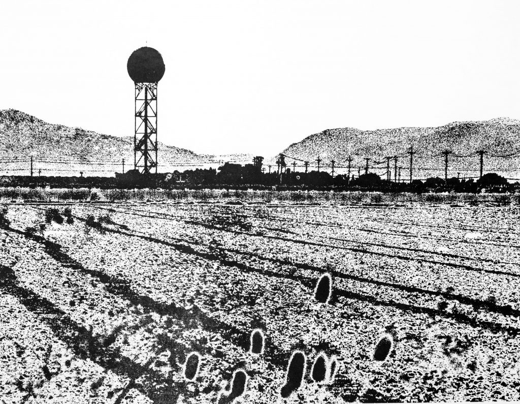 Black and white relief print of a landscape with furrows in the foreground, a doppler radar tower and power lines in the midground, and a mountain gap in the background.